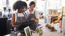 Two Women Working the Cash Register at a Cafe